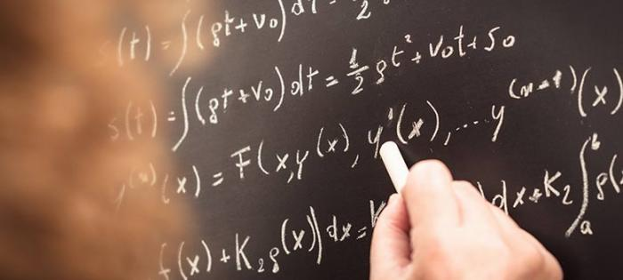 Person writing various formulas & equations on chalkboard